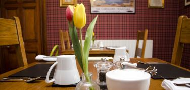 Breakfast table set up with slate place mats, white crockery and tulips in a bud vase at Strathallan Guest House