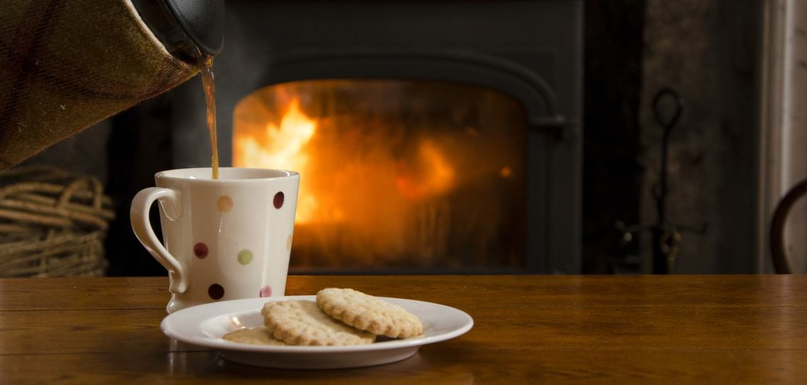 Cafetier pouring hot black coffee into a mug with multi coloured spots next to a plate with shortbread rounds in front of a roaring log burner