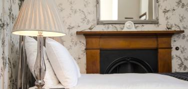 Pale beige lampshade on a bedside table lamp next to a bed with white linen in front of an oak surround fireplace