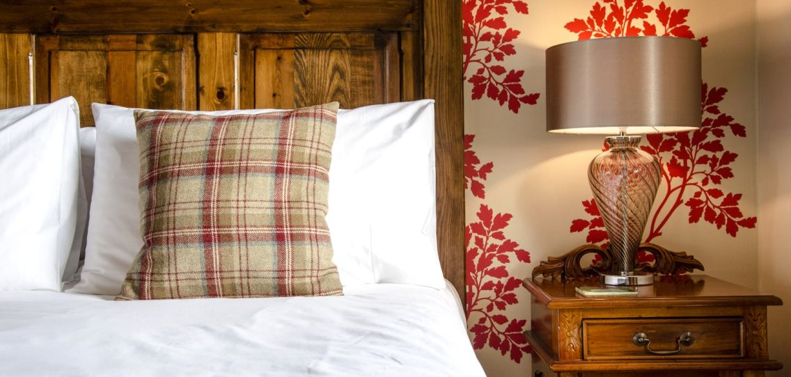 Pillows on a bed with a tartan cushion and a solid oak headboard, red leaf patterned wallpaper
