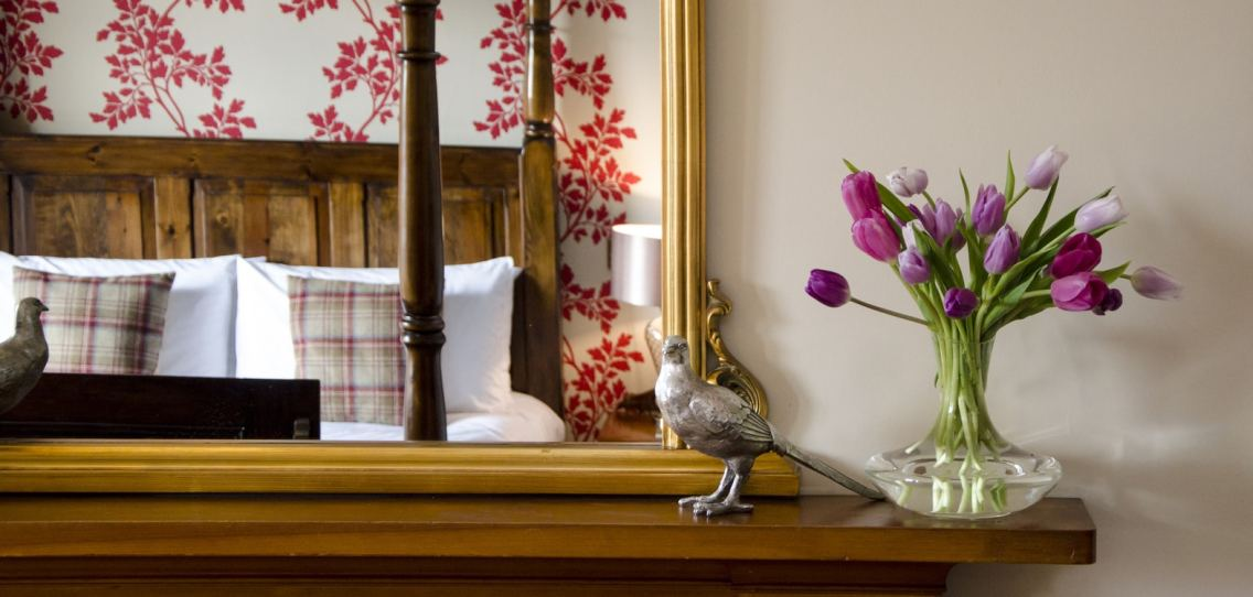Mirror showing a reflection of a four poster bed with red leaf patterned wallpaper and a vase of purple tulips