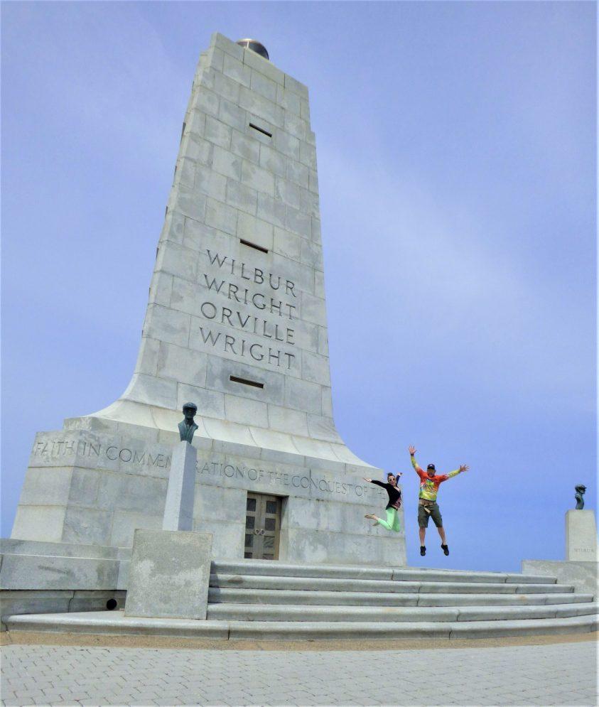 couple jumping at wright brothers memorial kitty hawk outer banks north carolina