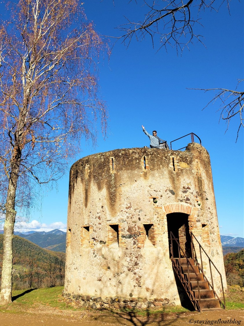 man waving from atop a tower backed by mountains