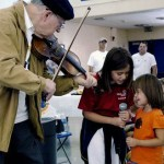 senior playing violin with young girl singer