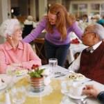 woman talking to 2 seniors