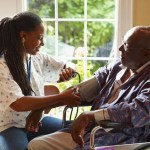 senior balck man recieves care from black caregiver