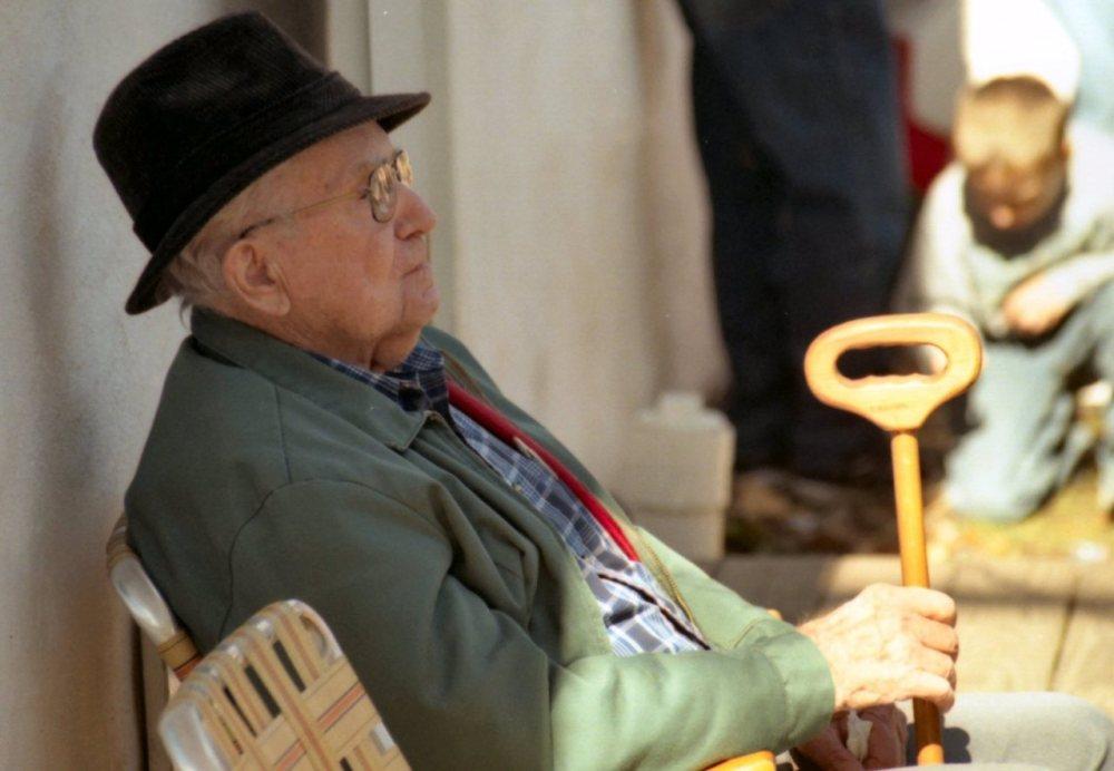 senior sitting with cane