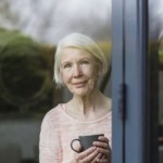 senior woman standing alone looks out window