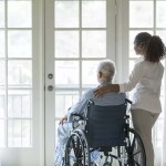 young caregver and senior patient in wheelchair gazing out window copy