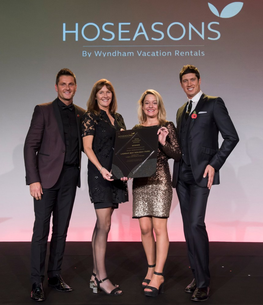 Celebration time as Ladram Bay takes to the winners podium at the Hoseasons conference. Left to right are Hoseasons managing director Simon Altham, Ladram Bay director Zoe House, park general manager Claire Williams, and TV presenter and awards host Vernon Kay