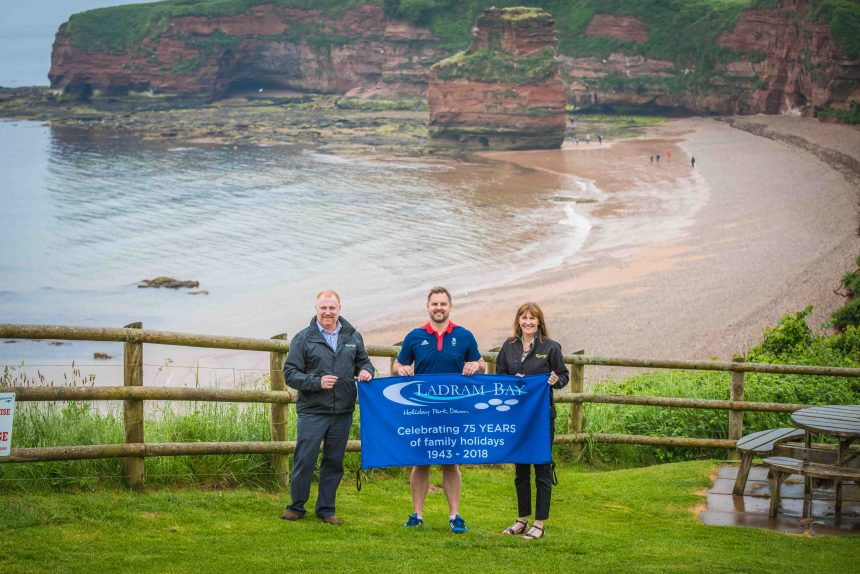 Happy anniversary: above the park's private beach, Liam helps unfurl the banner celebrating its 75 years