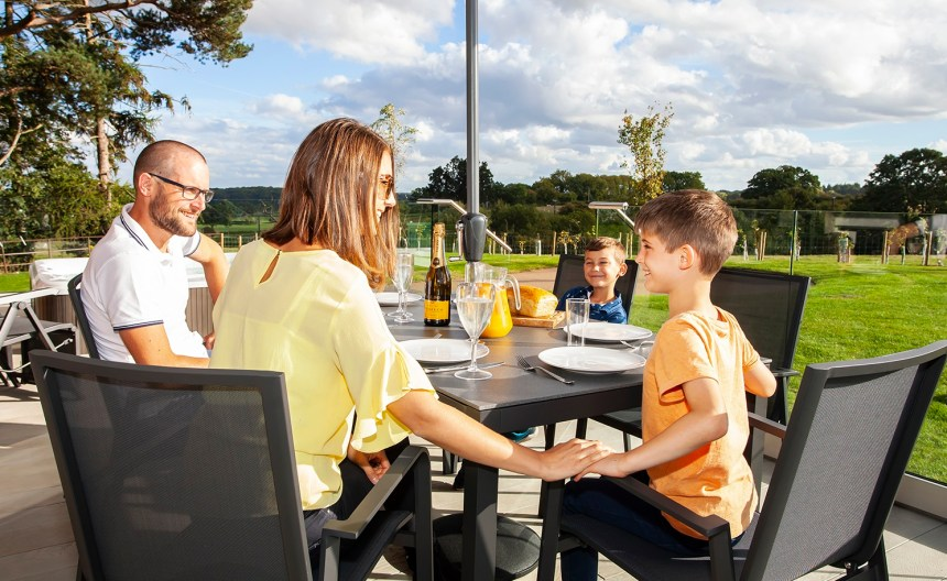 In another scene, the family relax on the lodge's decking with its far-reaching countryside views