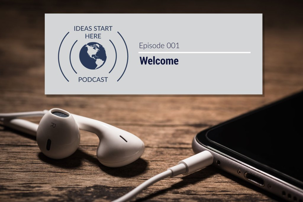 "Earbuds plugged into a smartphone with a sign that says, ""Ideas Start Here Podcast Episode 1: Welcome"""