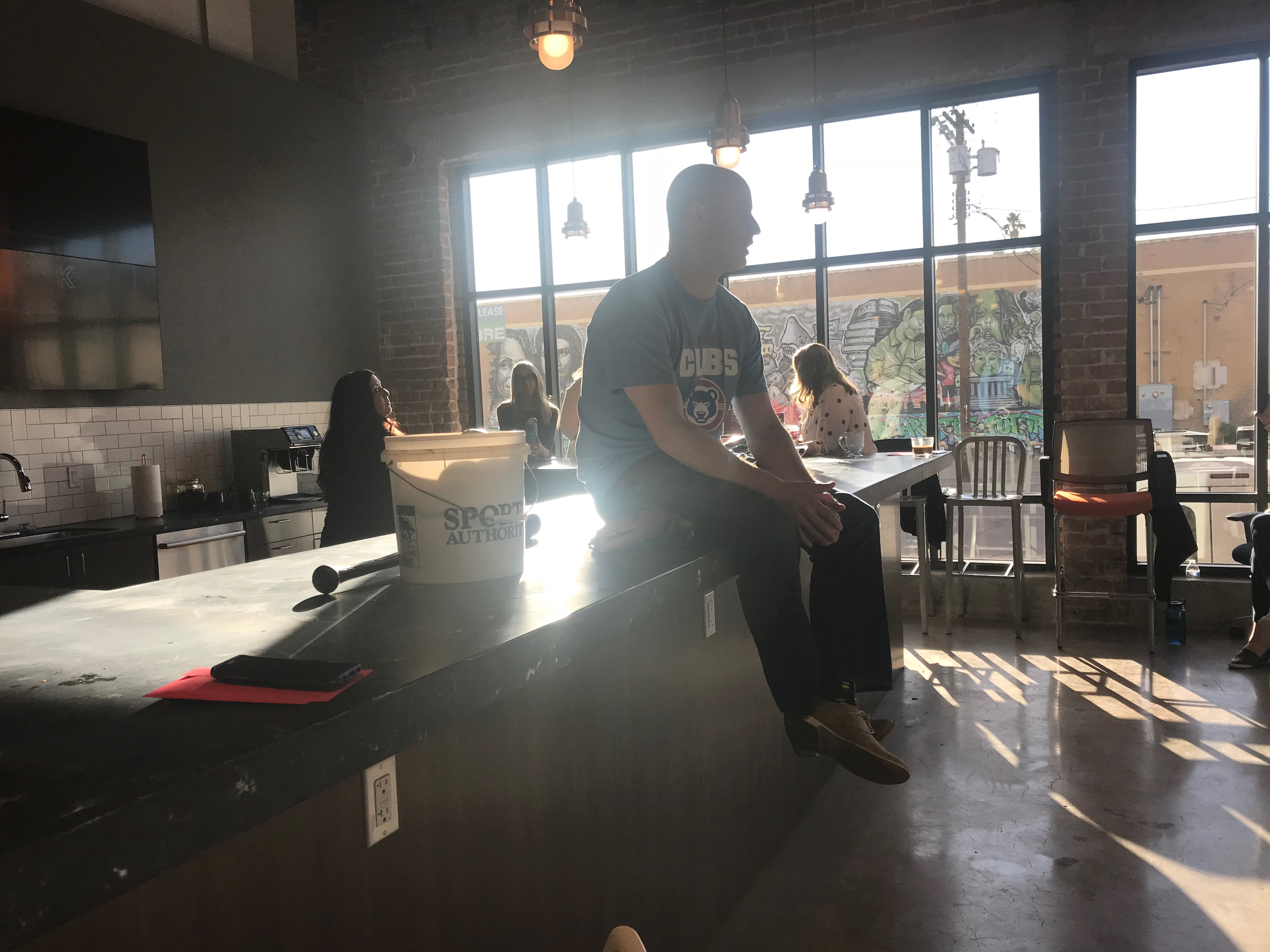 A male employee sits on the counter in the Ideas Start Here Cafe at STC, getting ready for a presentation, while several other employees eat lunch on barstools in a different area of the counter.