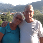 An older couple stand with their arms around each other in front of a summer mountain range