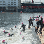 Women in wetsuits jumping into the river Thames