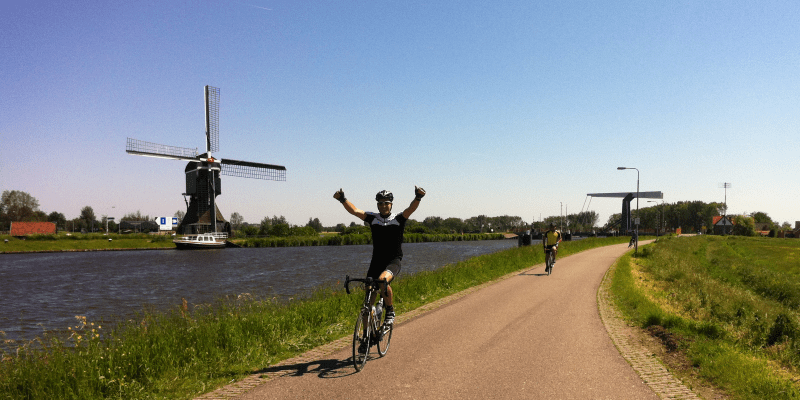 Cycling by a windmill and a river