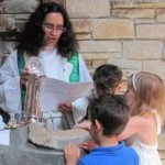 Rev. Miranda blessing the waters at the Baptismal Font, with kids gathered around in the foreground.