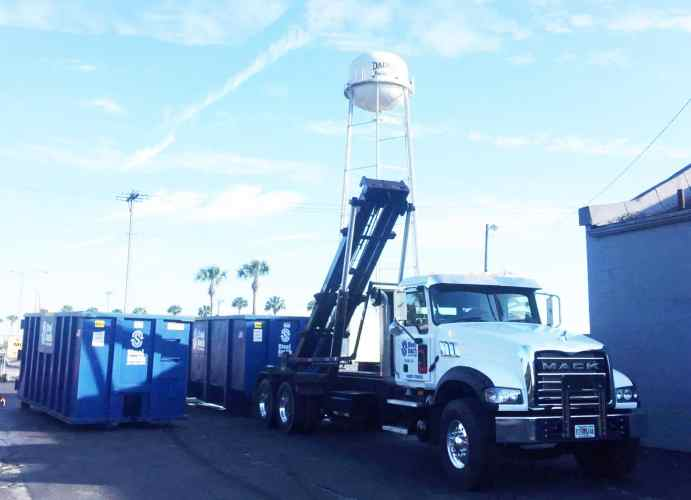 The SteelSmith roll off truck loading a dumpster for transport