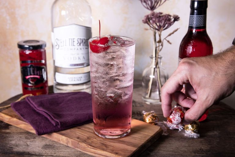A tall glass filled with Steel Tie Vodka, mixers and a cherry on top sitting on a wooden cutting board with a man's hand grabbing a wrapped chocolate truffle to the side