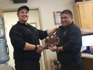 Captain Sam Sanders presents Engineer Angel Catindig, Jr. with a plaque for his two years of service.