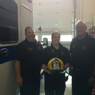 Firefighter Hughes receives her shield for completing her Jump Seat Qualifications.
