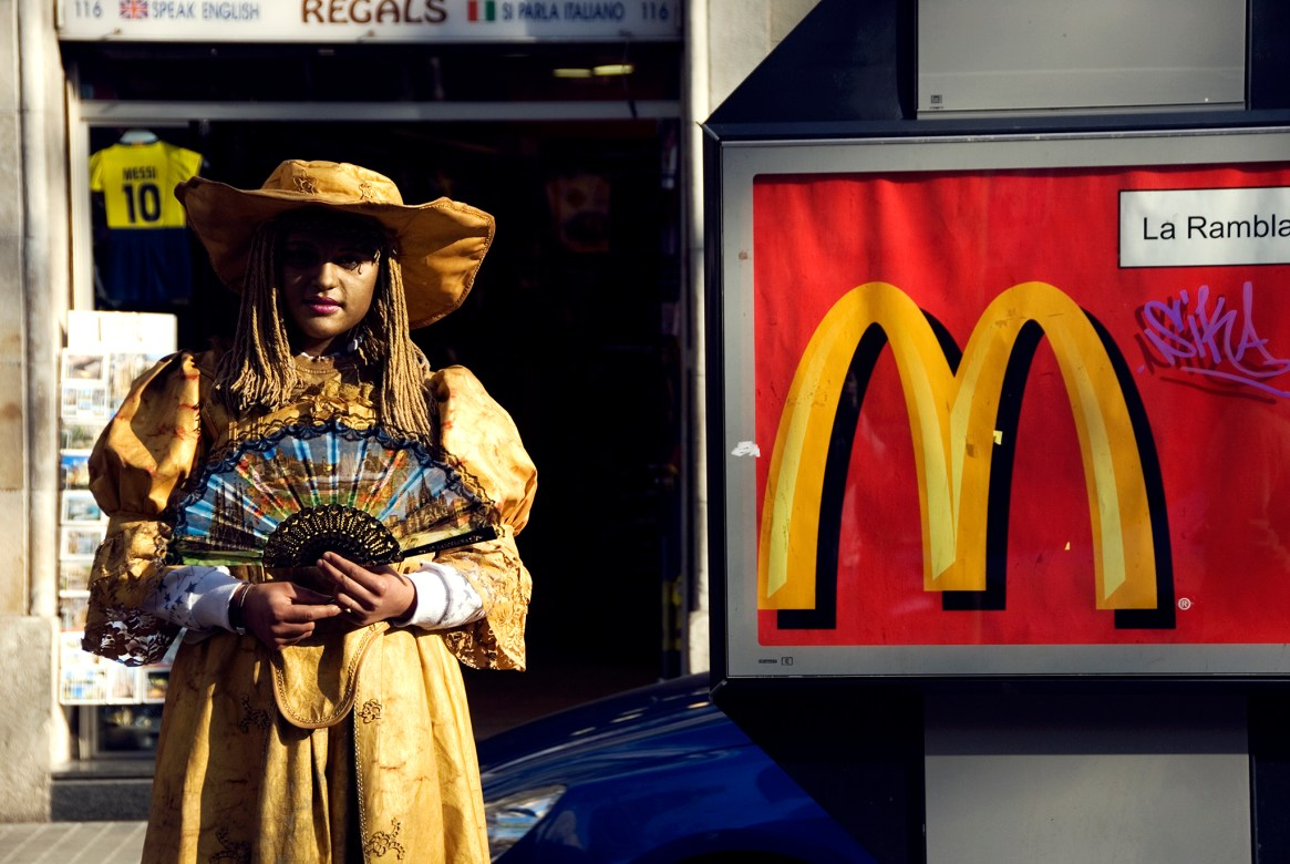 Human statue dressed in gold, standing next to a McDonalds sign