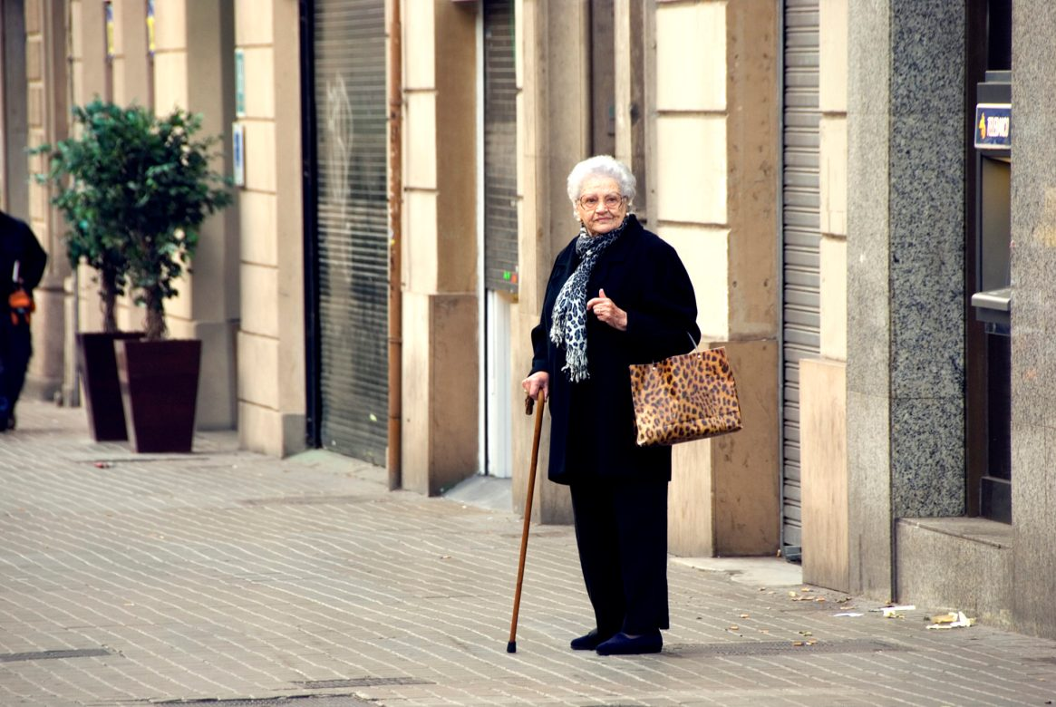 Old woman in black, pausing on the pavement with her walking stick