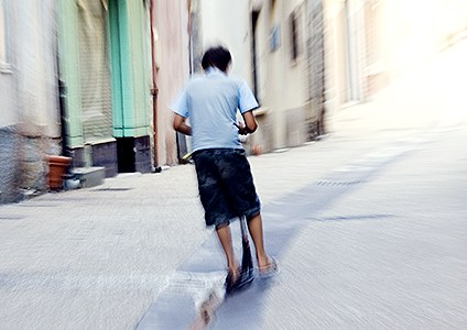 A boy on scooter speeding down an alleyway