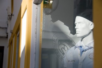 Male mannequin peering out of a shop window