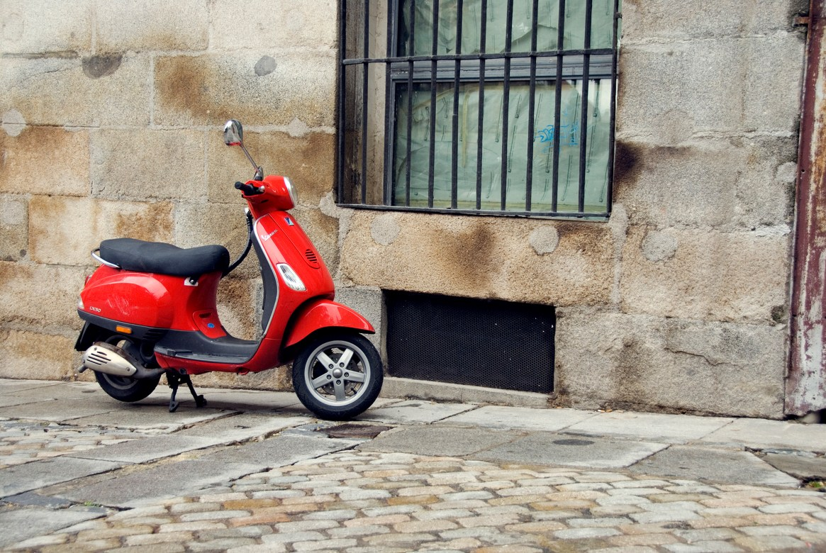 Red Vespa parked on cobble-stoned street in La Latina, Madrid