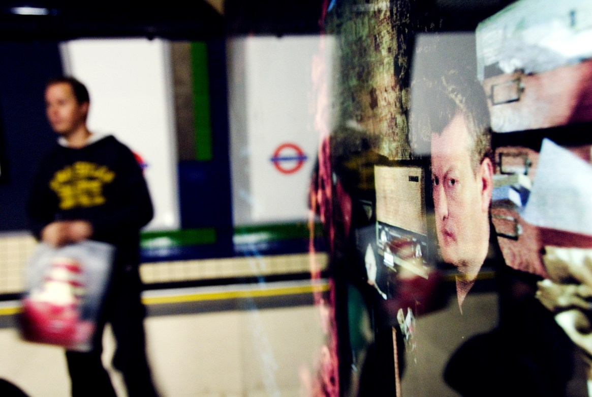Man on tube platform, with reflection in the glass covering a poster showing another man's face