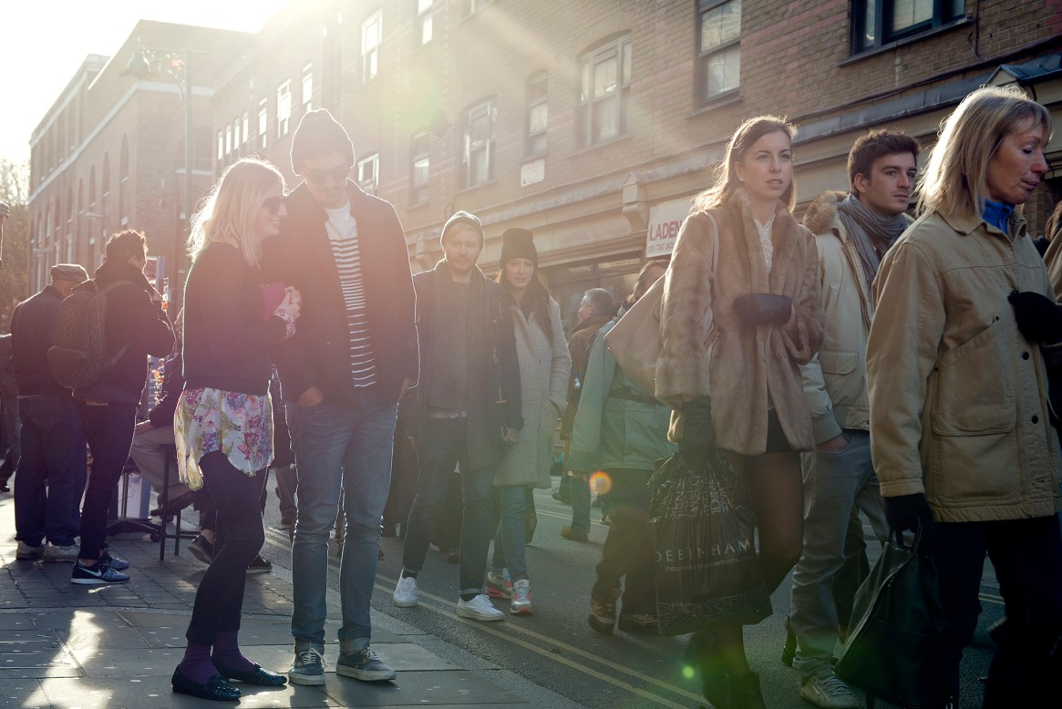 Backlit shot of mixed crowd meandering down Brick Lane on a sunny late afternoon