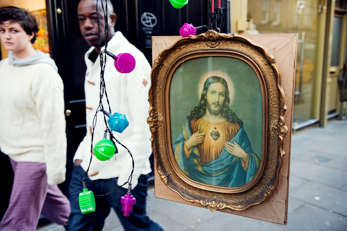A painting of Christ hangs at an antique dealer's stall on Brick Lane, with a man and woman walking past