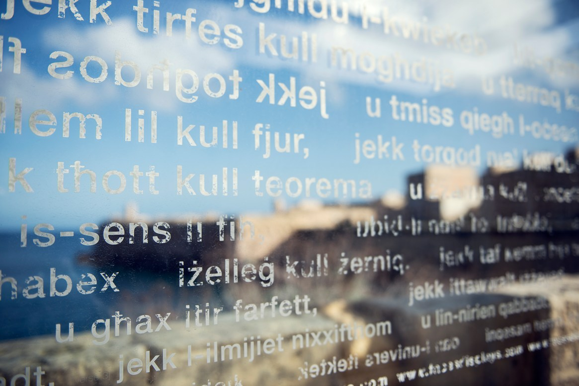 Valletta's old town seen through a glass pane covered in white text