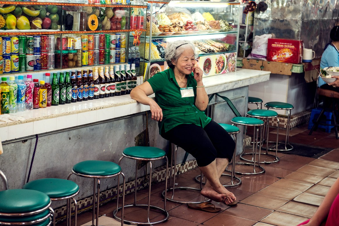 Old woman dressed in green and black sits on one of a row of green bar stools in front of her food and drink stall at a market in Ho Chi Minh City