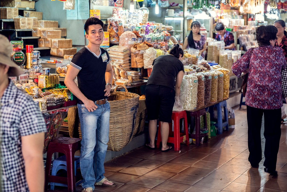 A young man in jeans and black t-shirt poses in front of his delicatessen stall at a market in Ho Chi Minh City