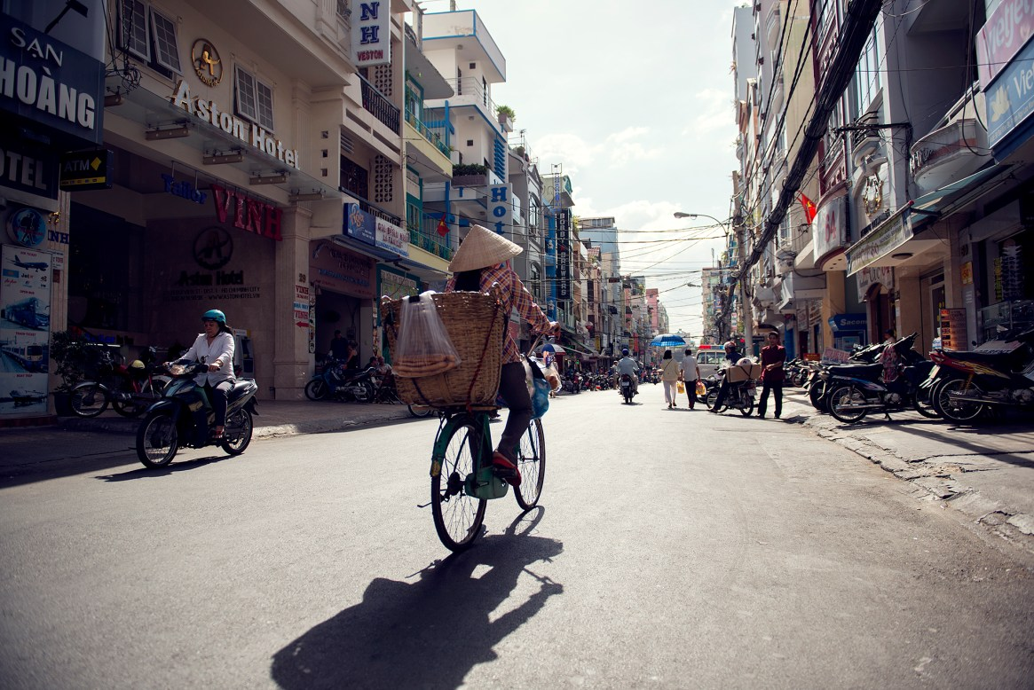 Female cyclist wearing a traditional Vietnamese hat in Ho Chi Minh City