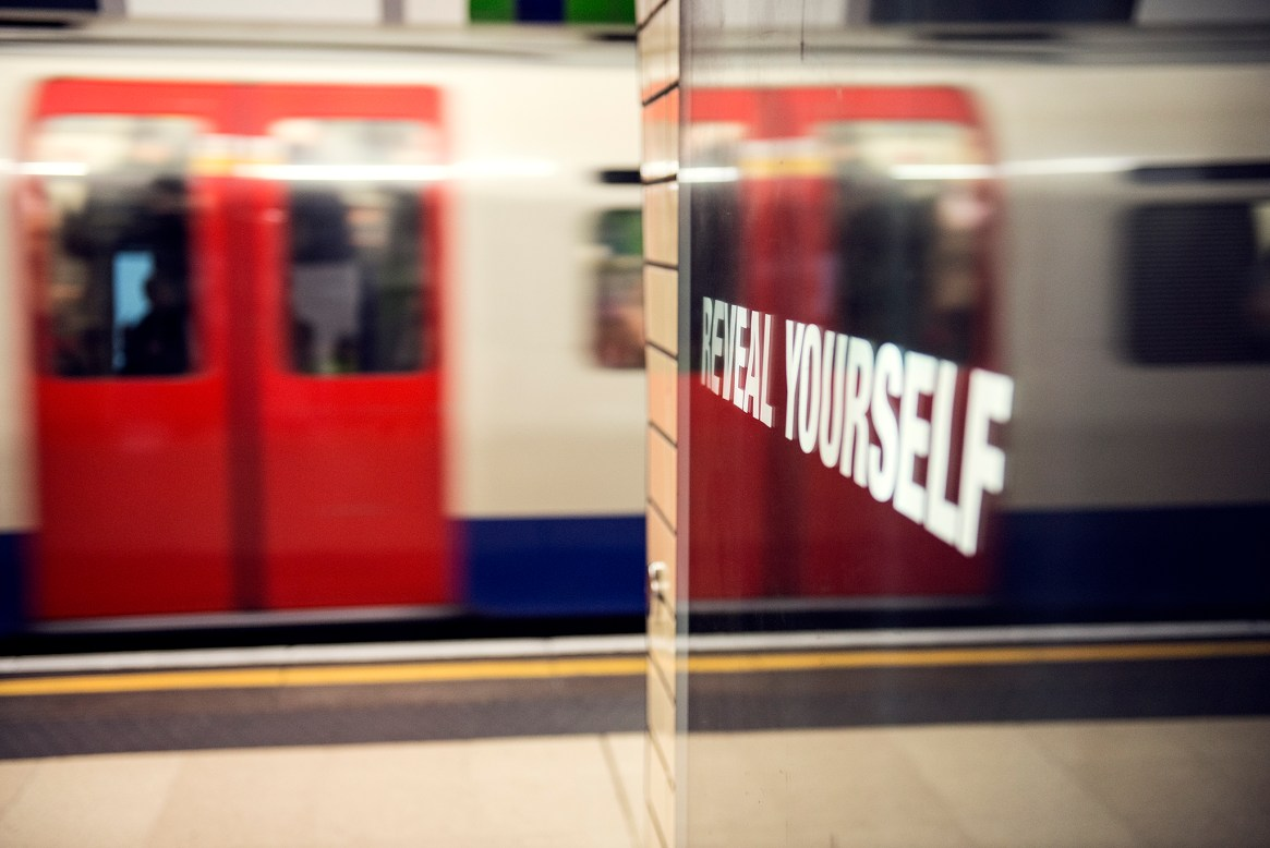"""A red tube carriage door is reflected in a black poster that reads """"reveal yourself"""""""