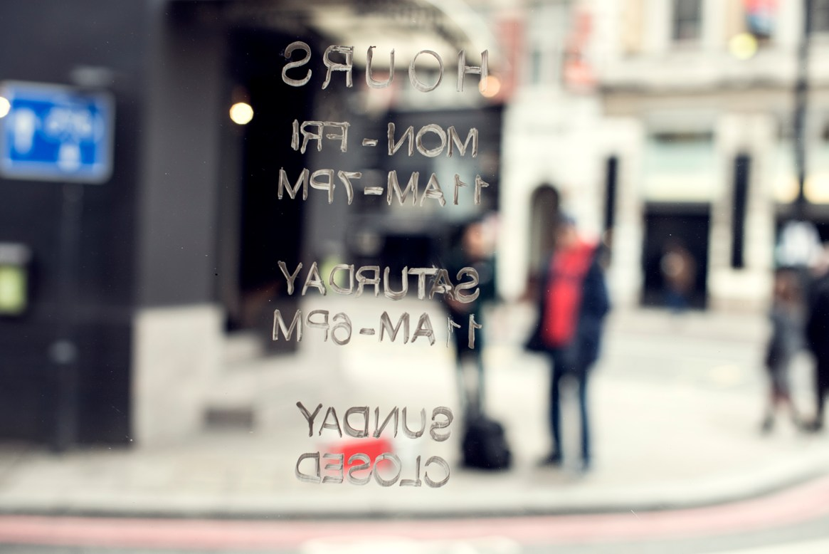 Two out-of-focus figures viewed through a glass door with shop opening hours written on it