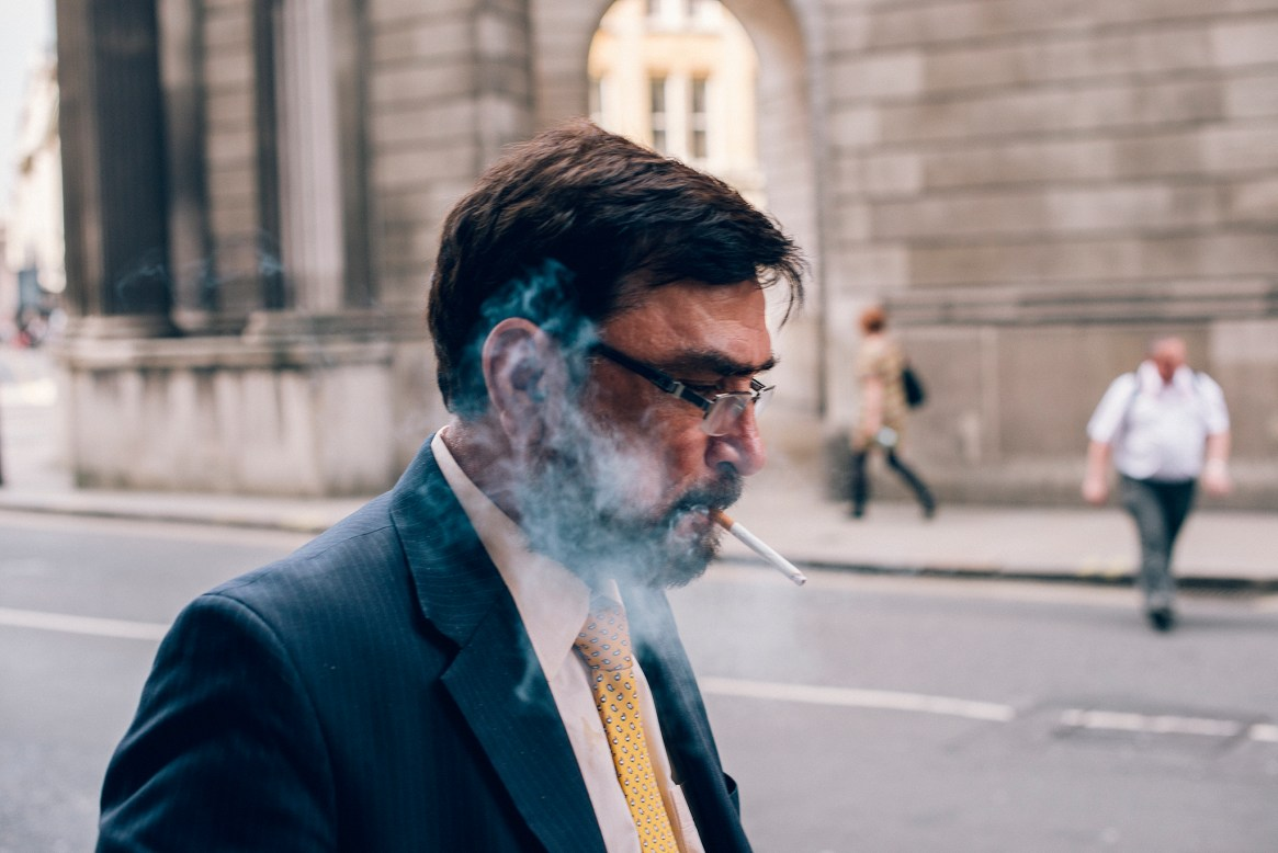 Close-up of a serious-looking suited office worker walking in the City of London whilst smoking a cigarette