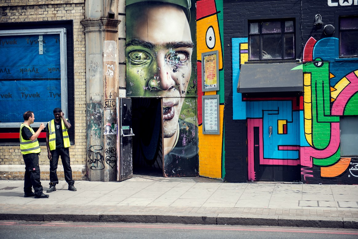 Two construction workers stand and talk on the pavement outside a building covered in quirky street art in Shoreditch, London