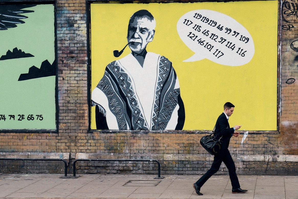 A man stars at his smartphone as he walks past a giant yellow poster of an old man with a speech bubble containing lots of numbers
