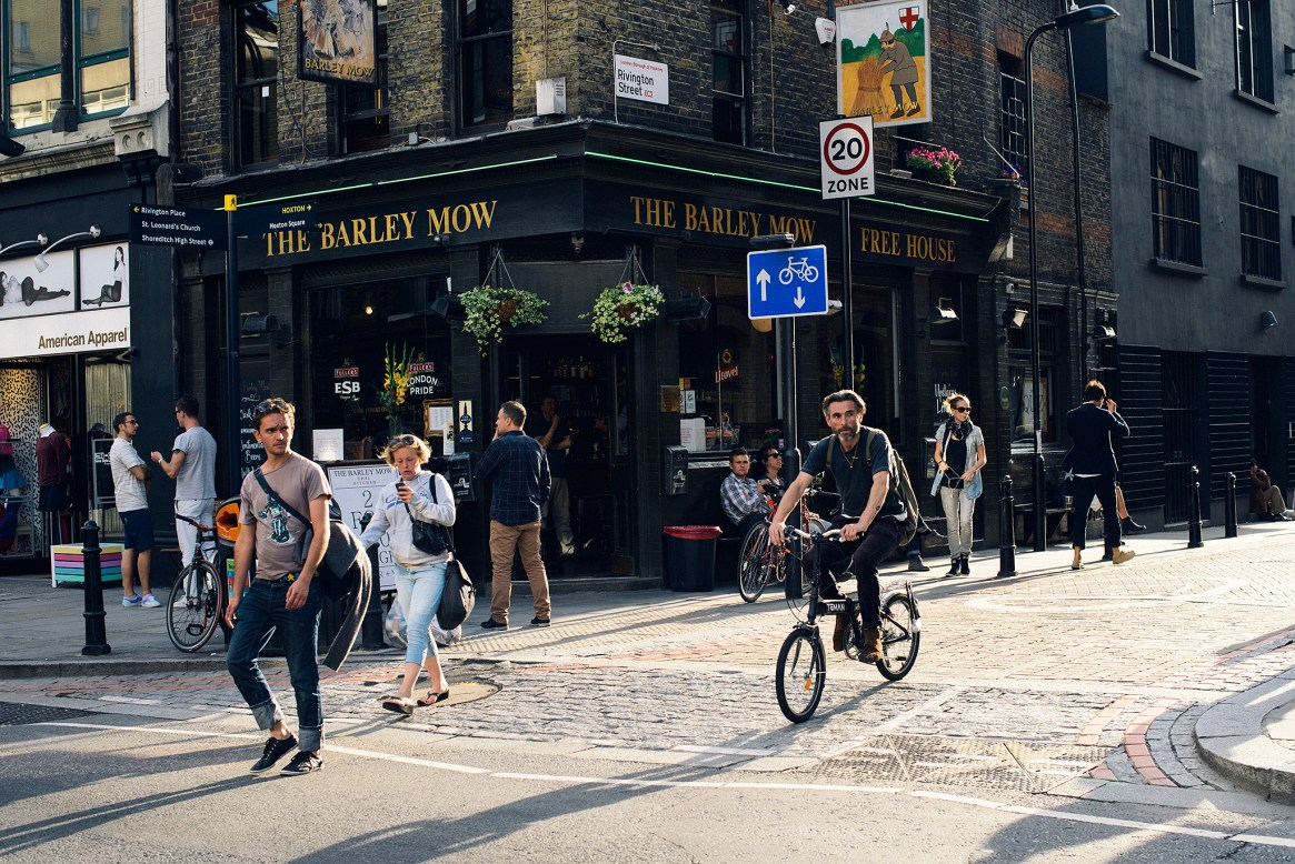 People walk past a pub called The Barley Mow on a sunny afternoon