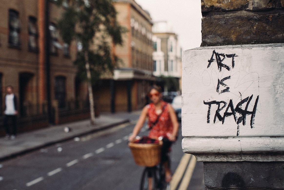 """A woman cycles past a wall with graffiti reading """"art is trash"""""""