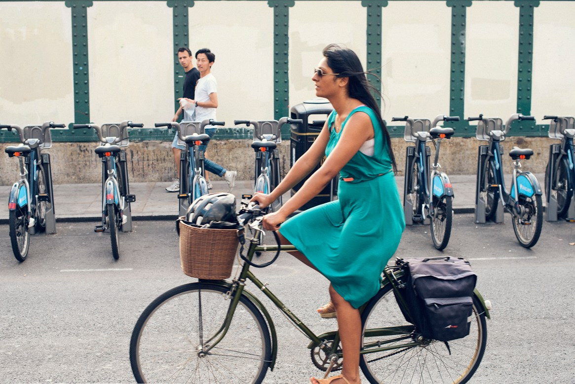 A woman in colourful green dress cycles past two young men walking past a row of cycles