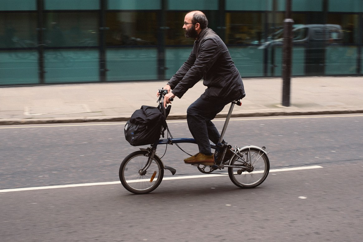 A man in office attire rides his folding commuter bike to work near Moorgate in the City of London