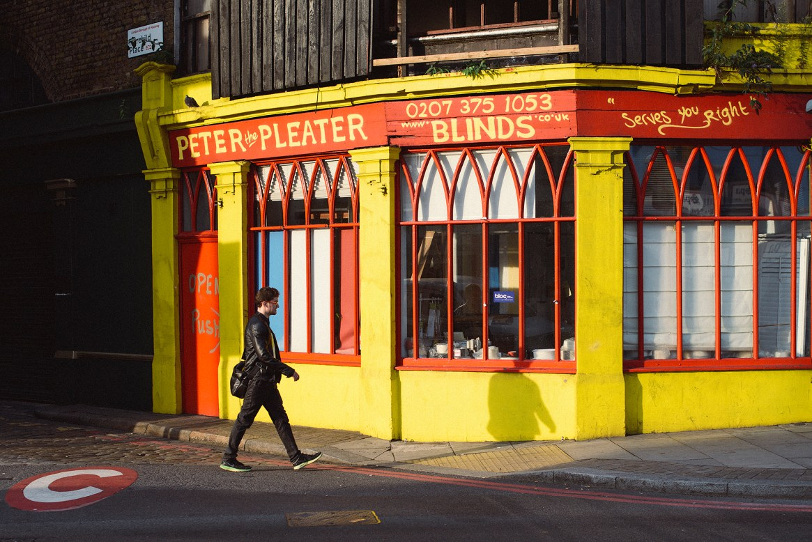 A man dressed in black trousers and leather jacket walks past a bright yellow and red blinds shop in Shoreditch, London