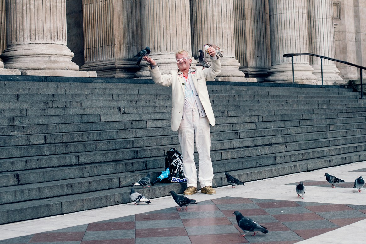 Wide shot showing a man wearing a white suit and glasses feeding pigeons - some of which are perched on his hands, arms and shoulders - on the steps outside of St Paul's Cathedral in London