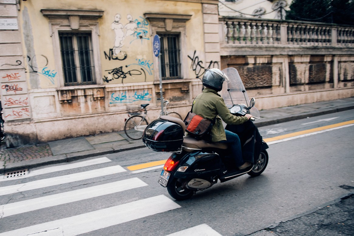 A man with a green jacket and grey helmet rides his blue Vespa down a street in the old town, Turin, Italy